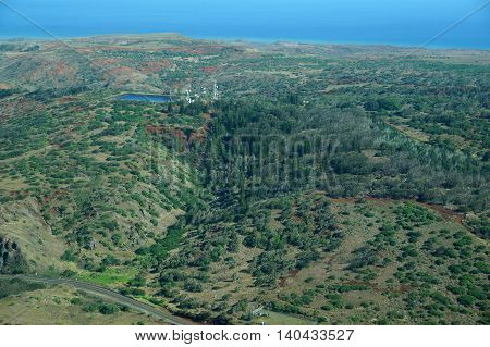Aerial of countryside running to the ocean with Water reservoir and communications towers on Molokai with roads largely undeveloped with trees and bushes. April 2016.