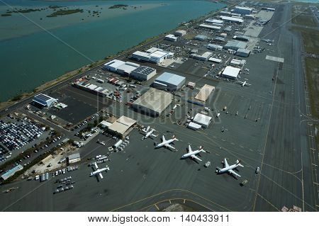 HONOLULU - APRIL 18: Aerial view of planes helicopters and cars parked by buildings by the runway at the Honolulu International Airport HNL next to the water on Oahu Hawaii. April 18 2016.