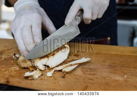 Closeup of the hands of a butcher cutting slices of meat off a large loin