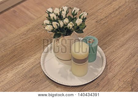 Candles and roses in a vase on a wooden table. Interior