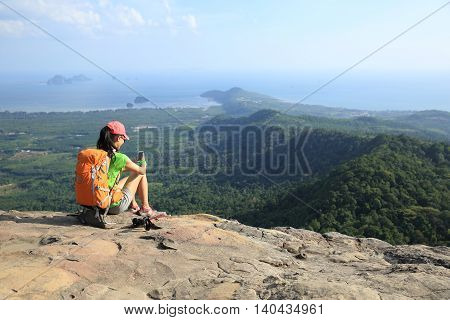 young woman backpacker use cellphone on mountain peak rock