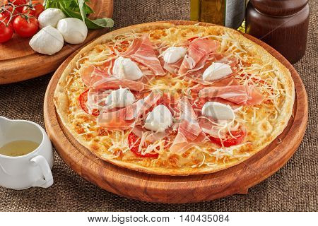 Pizza with bacon, tomatoes, pepper and mozarella