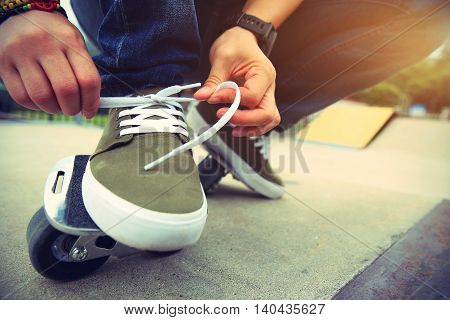 freeline skateboarder tying shoelace at skatepark ramp