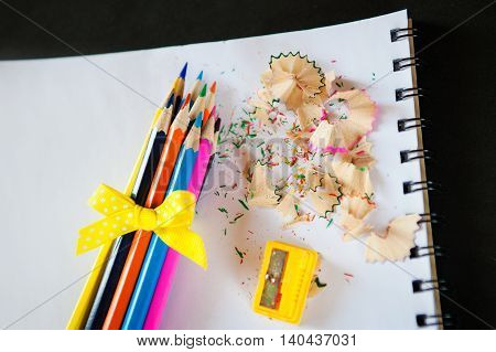 set of colored pencils bound bow with sharpener and shavings