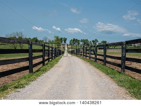 Low Angle of Gravel Farm Road between black fence