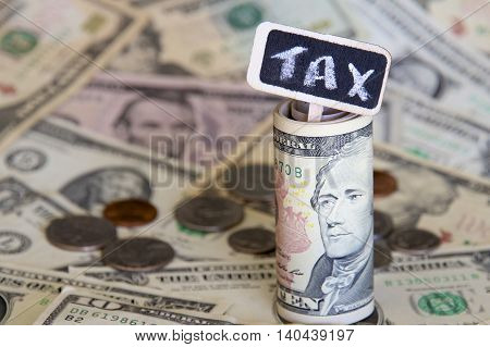 Tax sign with a background of American dollars.