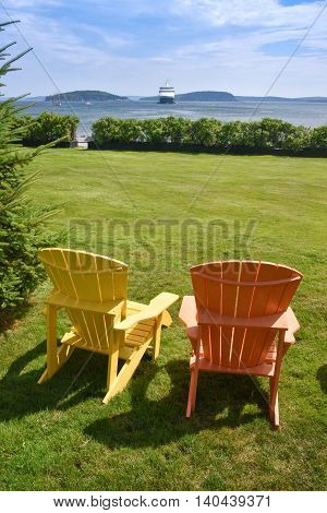 Relaxing scene with two chairs facing the harbor with a cruise ship