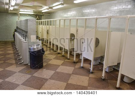 Rows of stalls and urinals in a public bathroom