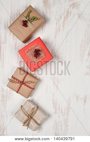 Four Christmas presents wrapped with different materials on a rustic white wood surface. Vertical format with copy space.