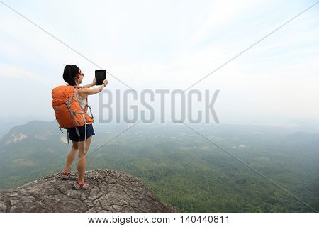 young woman backpacker taking photo on beautiful mountain peak