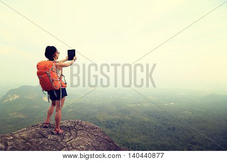 young woman backpacker taking photo on beautiful mountain peak