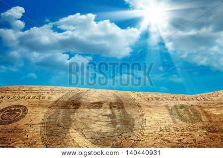 conceptual image of hundred dollar bill on dried cracked landscape
