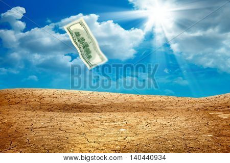 conceptual image of flying hundred dollar bill over dried cracked landscape