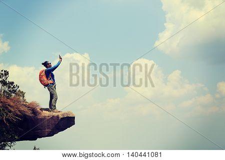 successful woman hiker taking photo on mountain top rock