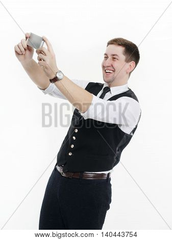 Businessman a waistcoat and tie making selfie photo on your smartphone. Isolated on white background.