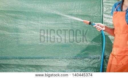 Watering garden equipment - hand holds the sprinkler hose for irrigation plants. Gardener working