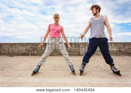 Outdoors activities sport and hobby. Exercises for healthy and strong body.. Friends stretch together have fun riding rollerblades.