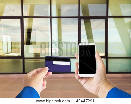 Isolated Hand With Credit Or Debit Atm Card And Smart Phone Or Mobile
