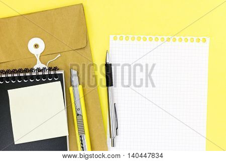 Envelope, Notepad, Empty Sheet Of Paper, Pen And Letter Opener On Yellow Desk