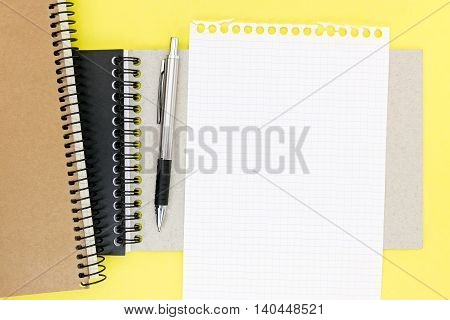 Empty Squared Sheet Of Paper From Notepad And Ballpoint Pen On Yellow Desk