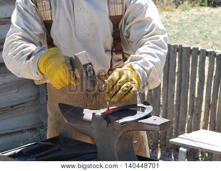 Male farrier working on a horseshoe outside.