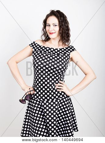 Beautiful young woman removes sun glasses, wears a dress with polka dots. expressing different emotions.