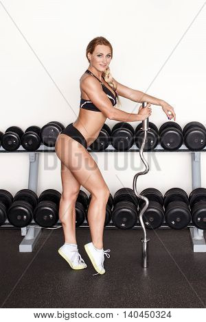 Blonde fitness woman posing with bar in gym