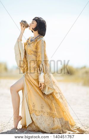 Fashion Stylish Beauty Portrait Holding and Drinking Cup. Girl standing in golden dress outdoors in desert. Hot sunny weather