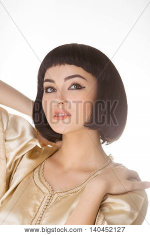 High fashion look. Glamorous closeup portrait of beautiful sexy stylish brunette young woman model with bright makeup with perfect clean skin in gold dress posing against bright gray background. Cleopatra