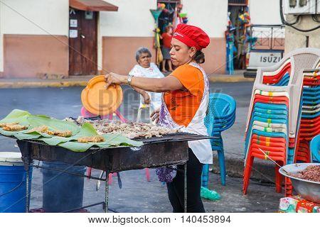 Leon Nicaragua - December 14 2015: food seller on street. Girl selling typical food on street