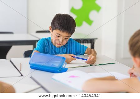 Schoolboy studying in classroom at school