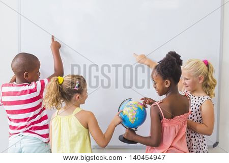 Kids studying globe in classroom at school