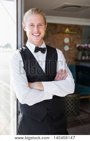 Portrait of waiter with arms crossed standing in restaurant