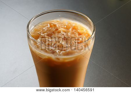 Glass of milky coffee with ice in asia on grey background