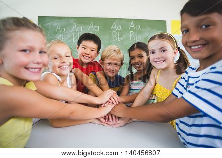 Portrait of school kids stacking hands in classroom