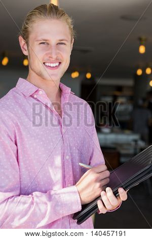 Portrait of restaurant manager holding organizer in restaurant
