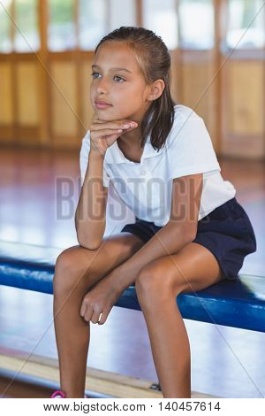 Close-up of thoughtful schoolgirl sitting in basketball court at school gym