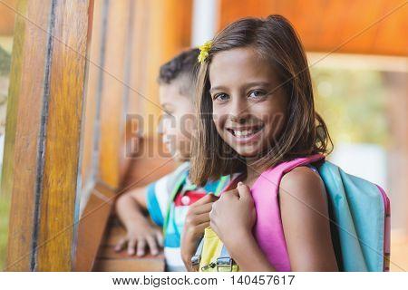 Portrait of smiling school girl standing in school corridor