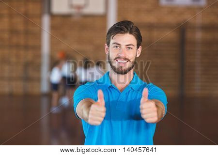 Portrait of sports teacher showing thumbs up in basketball court at school gym