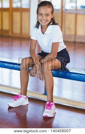 Portrait of happy schoolgirl sitting in basketball court at school gym