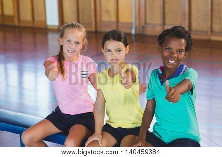 Portrait of girls smiling and making a thumbs up sign in basketball court at school gym