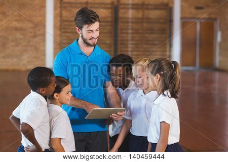 Sports teacher and school kids using digital tablet in basketball court at school gym