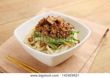 Udon noodle with minced beef and vegetables in white bowl on tablecloth