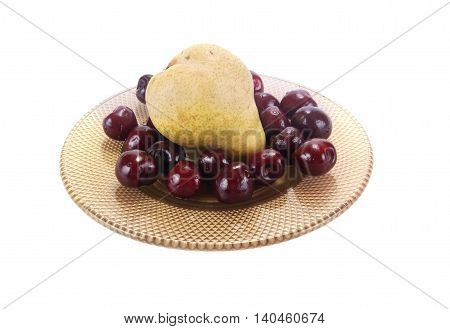 Berries cherries and ripe pear on a saucer on a white background