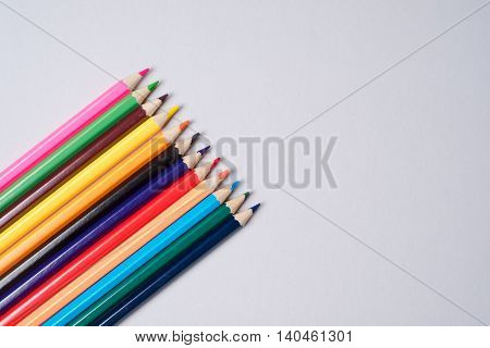 Colorful crayon pencils organized in a row over a white background above view