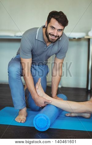 Physiotherapist giving leg massage to a woman on exercise mat in clinic
