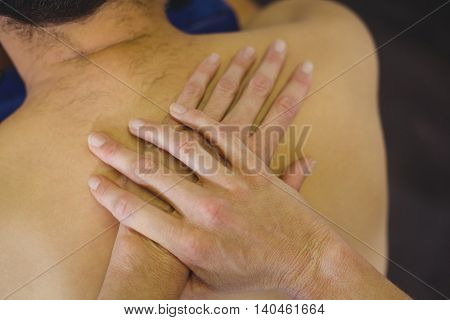 Close-up of physiotherapist giving back massage to a patient in the clinic