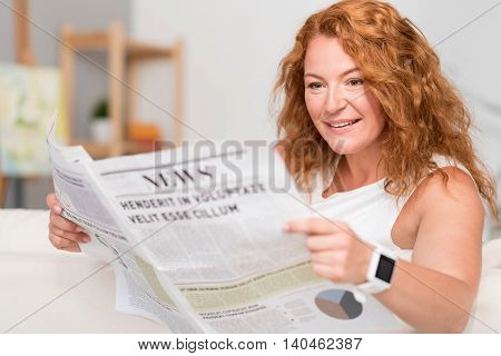 Information gap. Joyful pleasant adult woman smiling and reading newspaper while sitting on the couch