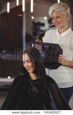 Hairdresser showing woman her haircut in mirror at salon