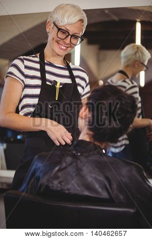 Smiling hairdresser interacting with client at a salon